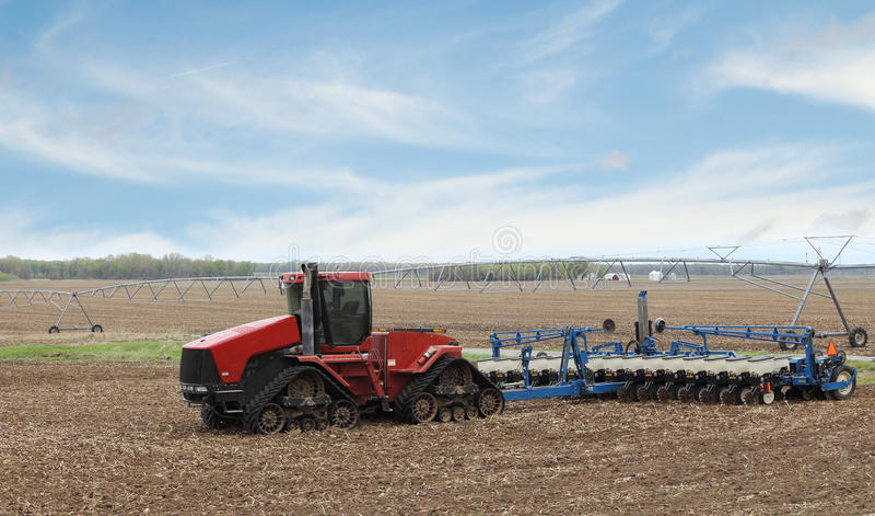 Röd lantgårdtraktor och Planter royaltyfria foton