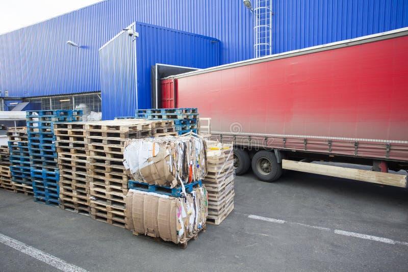 Röd lastbil som urladdar gods i lager arkivfoton