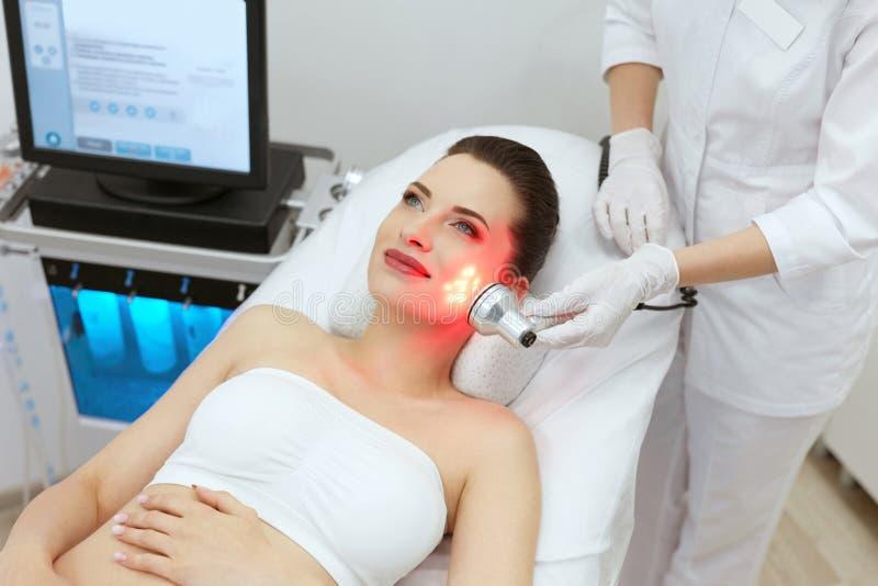 Röd ledd ljus behandling Kvinna som gör ansikts- hudterapi arkivfoto