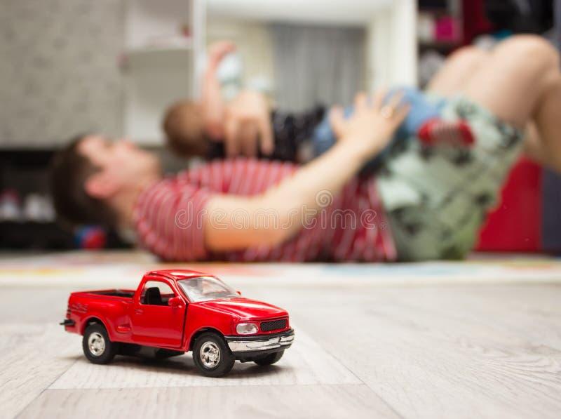 Röd leksakbil, fader och son som spelar på bakgrund arkivfoto