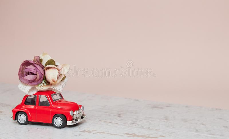 Röd leksakbil med blommor på ligthbakgrund royaltyfri foto