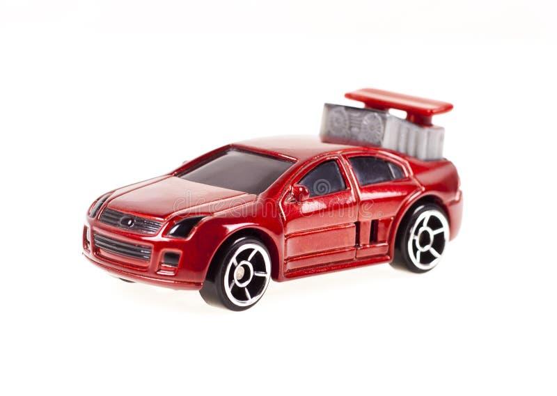 Röd leksakbil på den vita bakgrunden arkivfoton