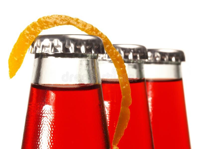 Röd lemonad med den orange vridningen i flaskor på vit bakgrund arkivbild