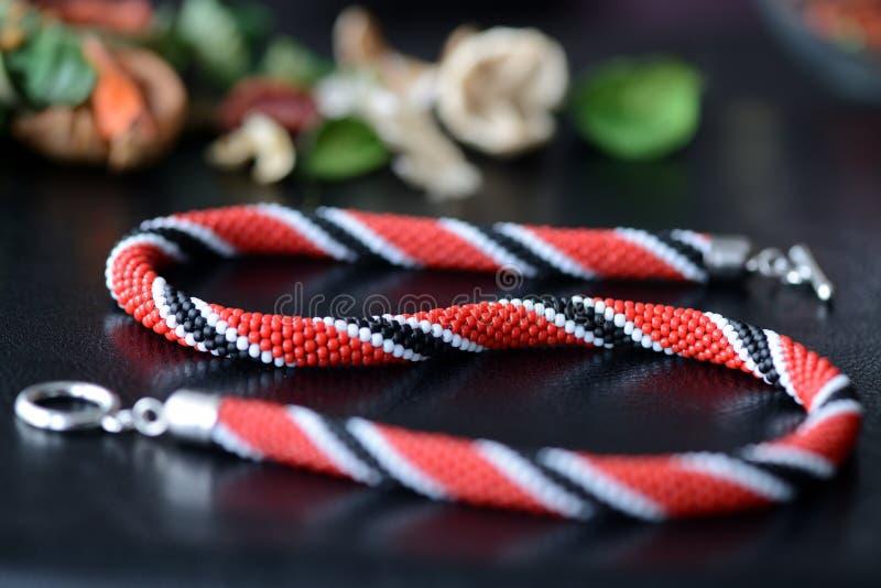 Röd ljus prydd med pärlor halsband, svartvita färger på en mörk bakgrund royaltyfri bild