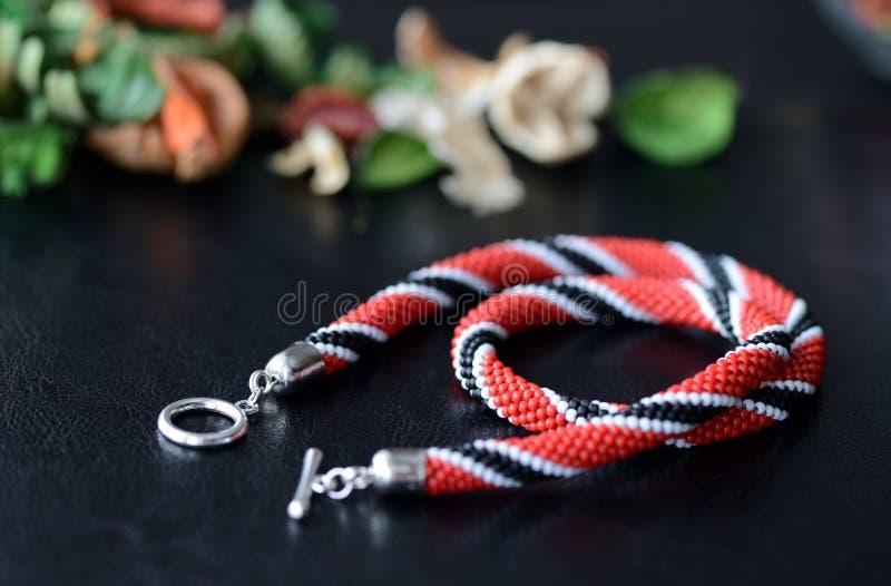 Röd ljus prydd med pärlor halsband, svartvita färger på en mörk bakgrund arkivfoton