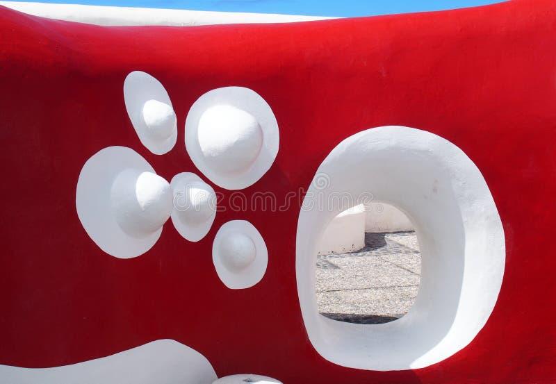 Röd målad krökt betongvägg med vita detaljer fotografering för bildbyråer