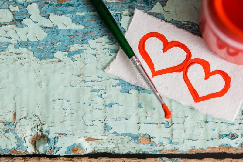Röd målarfärggouache i en krus, borste målat två hjärtor på en rest av papper på en texturerad gammal sprucken bakgrund för blå g arkivfoton