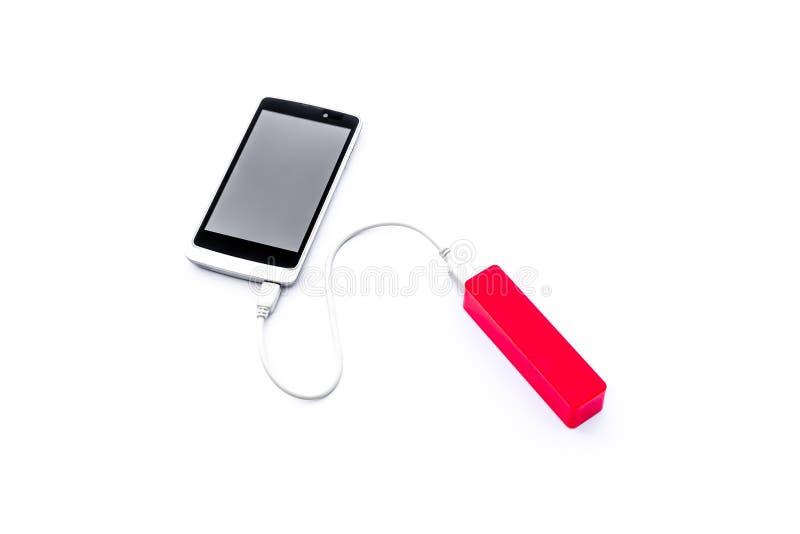 Röd maktbank och laddande mobiltelefon som isoleras på vit backg arkivfoto