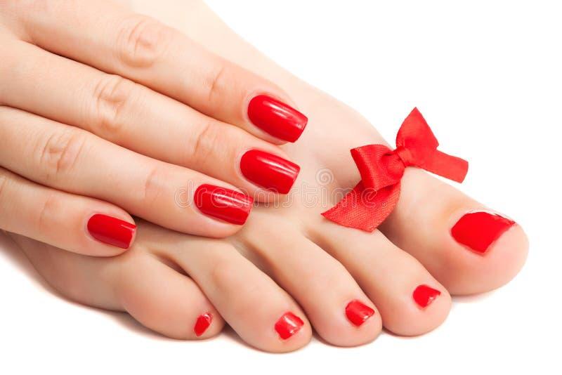 Röd manicure och pedicure med en pilbåge. isolerat royaltyfri bild