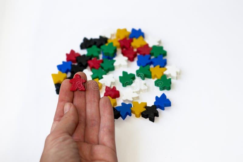 Röd meeple för Closeup ovanför gruppen av färgrika delar av brädeleken på vit bakgrund Förbereda sig för roligt gameplay Begrepp royaltyfri bild