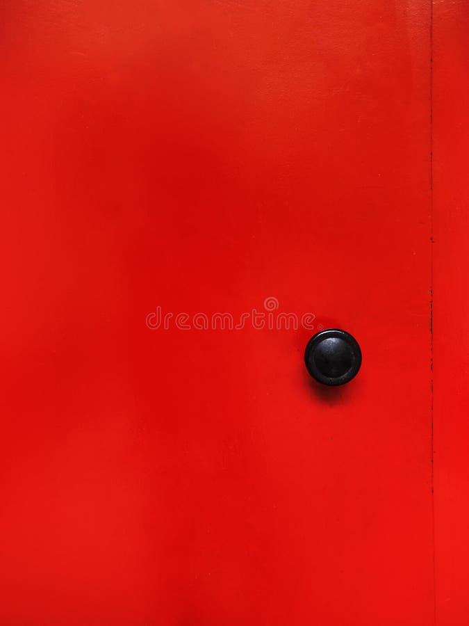 Röd metalldörr med det svarta handtaget royaltyfria bilder