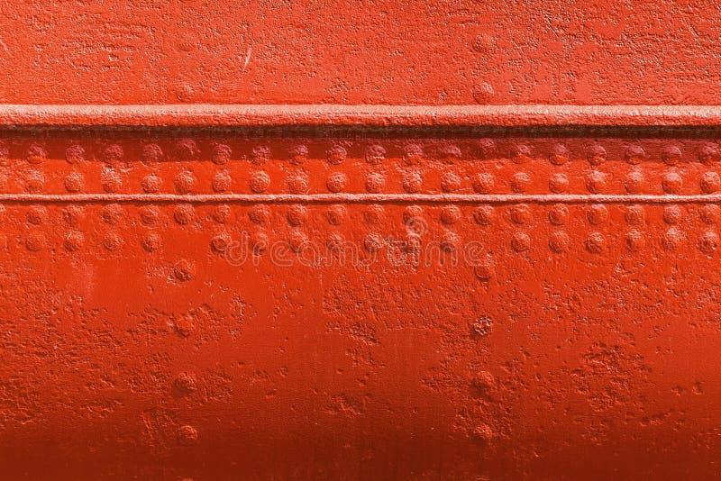 Röd metallväggtextur med sömmar och nitar arkivfoto