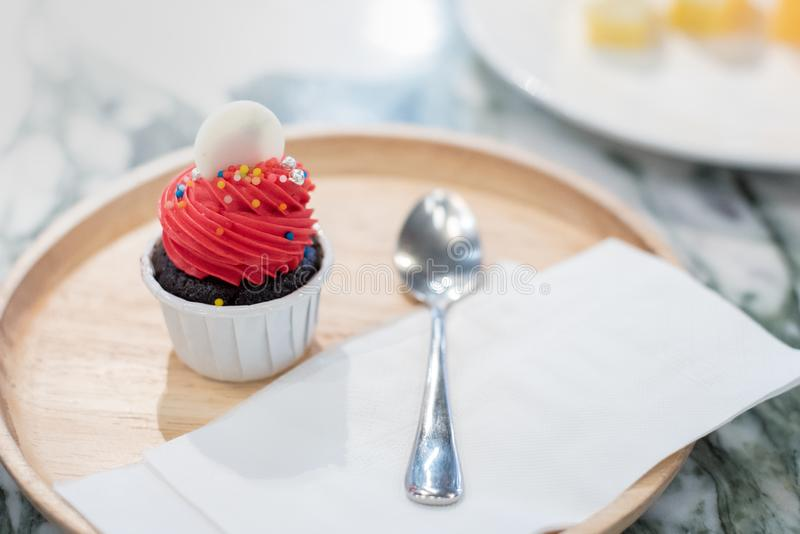 Röd mini- kaka och brun muffincirkel som är vit överst i den vita koppen träplatta med skeden och silkespapperpapper på tabellen royaltyfria foton
