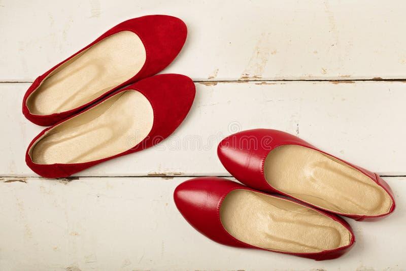 Röd mockaskinn- och läderkvinna` s skor ballerina på träbackg arkivbilder