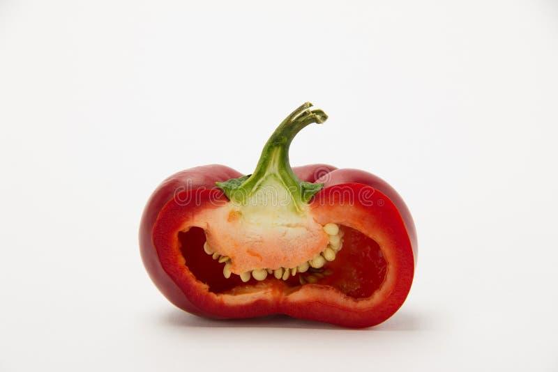 Röd mogen söt peppar i ett snitt på en vit bakgrund arkivbild