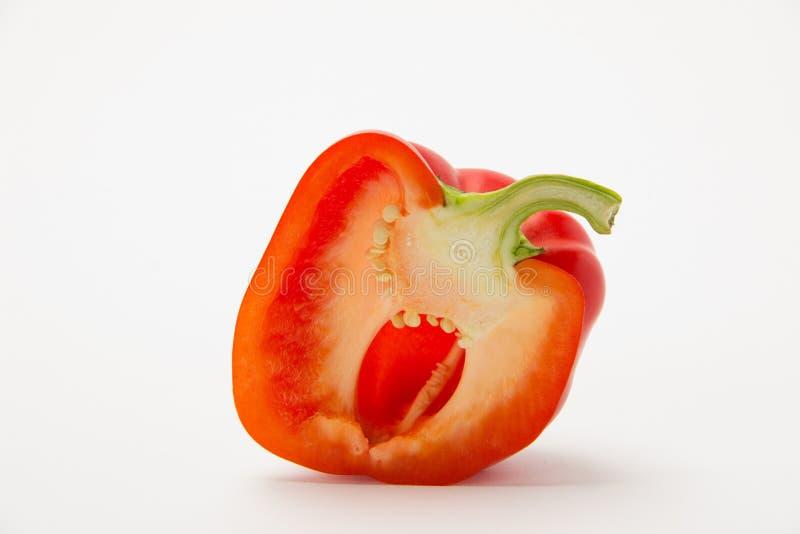Röd mogen söt peppar i ett snitt på en vit bakgrund arkivfoto