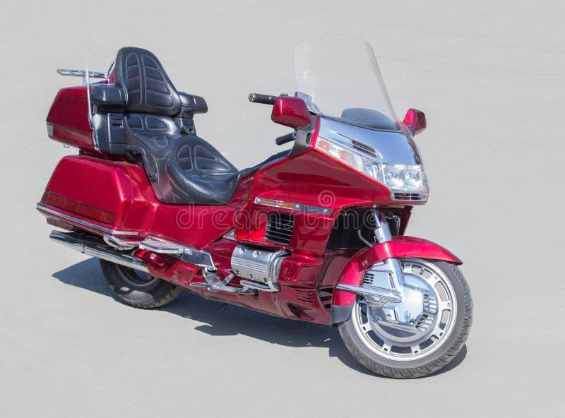 Röd motorcykel på asfalt arkivbild