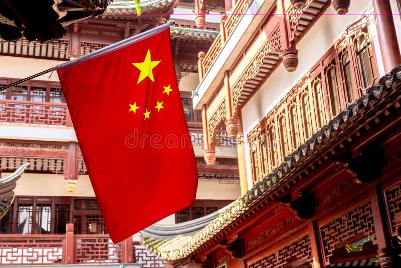 Röd nationsflagga av Kina mot gamla kinesiska byggnader på den Yuyuan trädgården i Shanghai, Kina royaltyfria bilder
