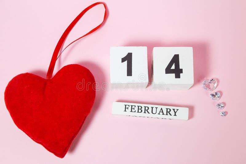 Röd och crystal hjärta och träkalender på den rosa bakgrunden arkivbilder