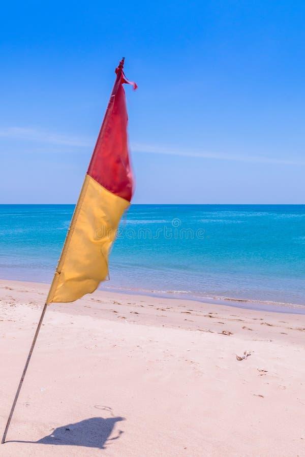 Röd och gul flagga på stranden fotografering för bildbyråer