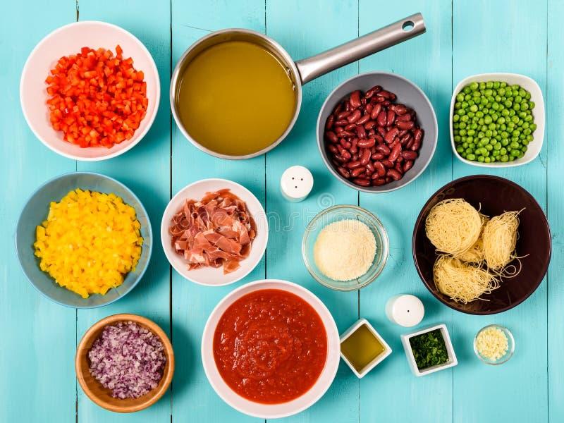 Röd och gul paprika, lök, bacon, grönsakmateriel, ketchup, bönor och ärtor och ingredienser för vermicellerpastamat royaltyfria foton