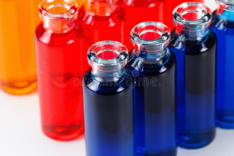 Röd och orange flytande för blått, i kemiska labbprovrör på vit bakgrund arkivfoto