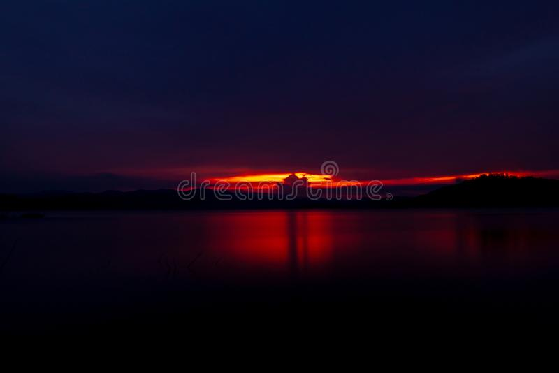 Röd och purpurfärgad solnedgånghimmel på berget och sjön h?rlig aftonsky Majest?tisk solnedg?nghimmel mot bakgrund field bl?a okl royaltyfri bild