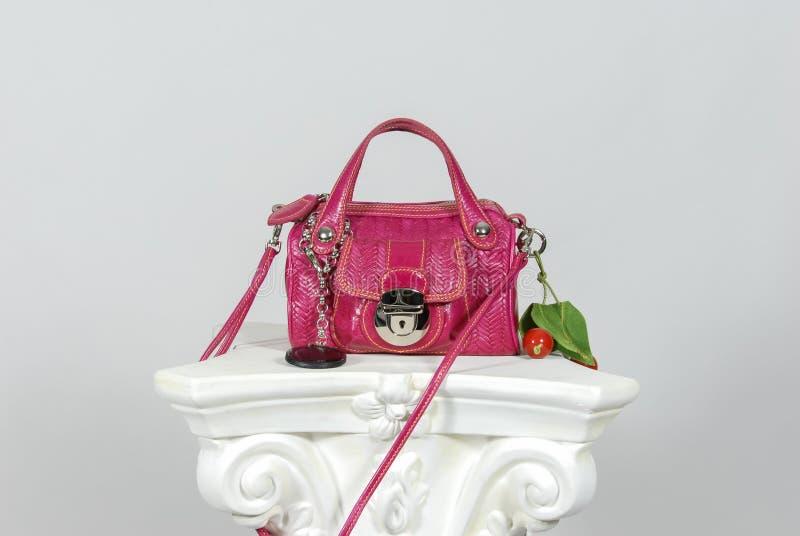 Röd och rosa färgläderhandväska på grekisk kolonn royaltyfri bild