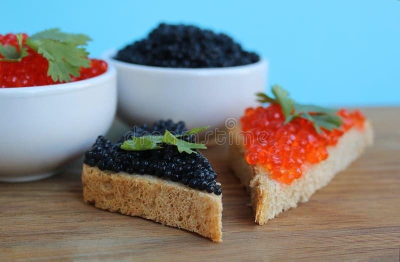 Röd och svart kaviar av fisklögner på rågbröd royaltyfria foton