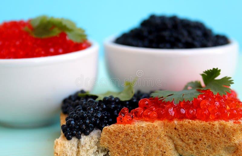 Röd och svart kaviar av fisklögner på rågbröd arkivbild
