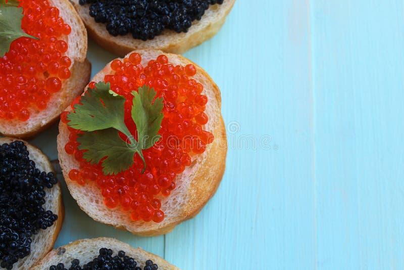 Röd och svart kaviar av fisklögner på vetebröd arkivbild