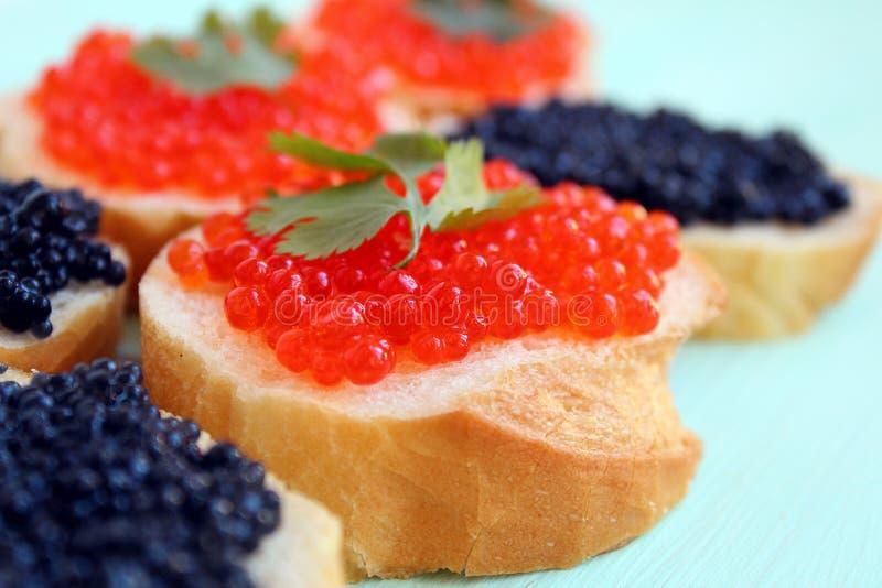 Röd och svart kaviar av fisklögner på vetebröd arkivfoto