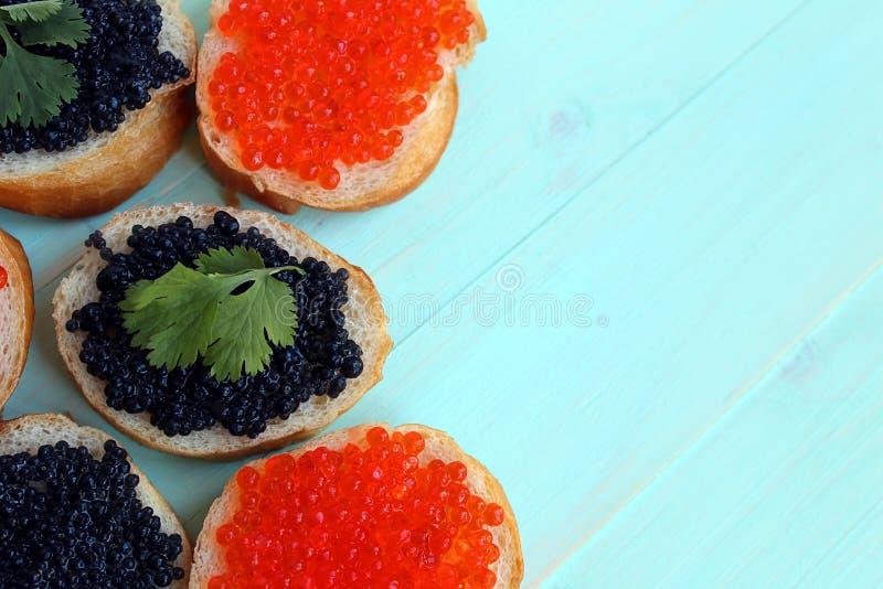 Röd och svart kaviar av fisklögner på vetebröd royaltyfri foto