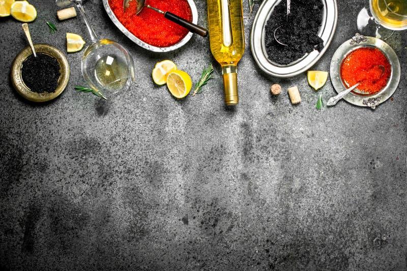 Röd och svart kaviar med vin och citroner arkivbild