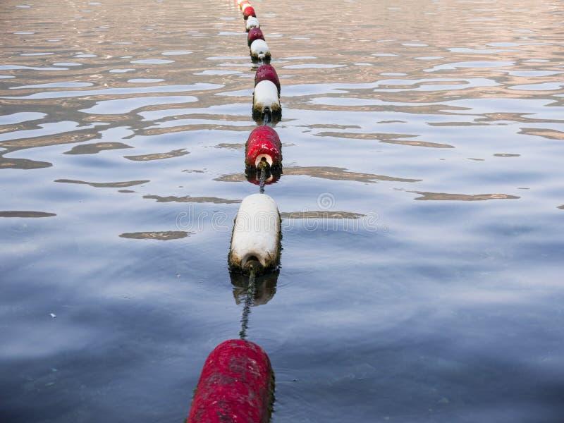 Röd och vit bojlinje i havsvatten arkivfoton