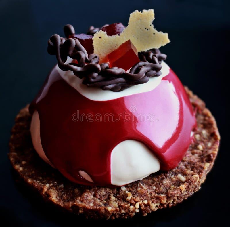 Röd och vit efterrätt med chokladgarnering, röd gelé och kakagrunden royaltyfria bilder
