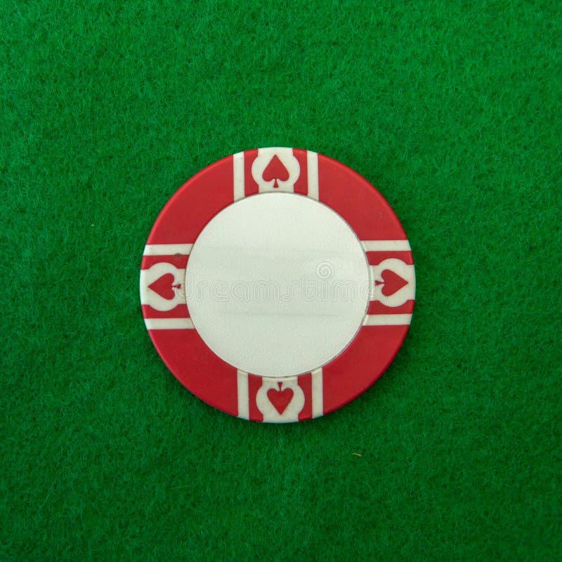 Röd och vit kasinochip på gräsplan royaltyfri bild