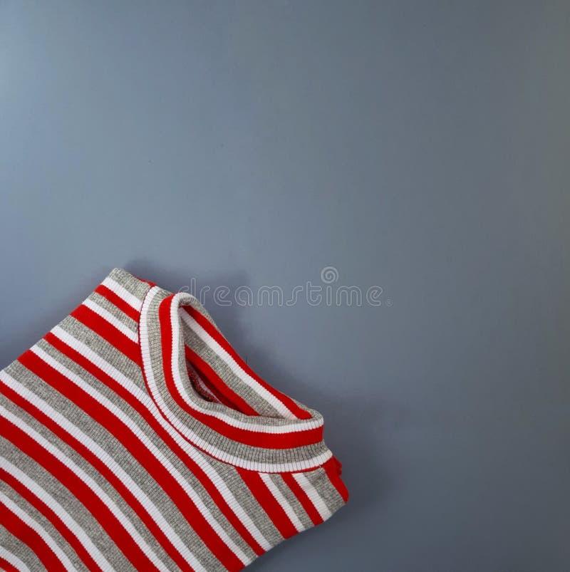 Röd och vit linnetröja på grå bakgrund royaltyfri foto