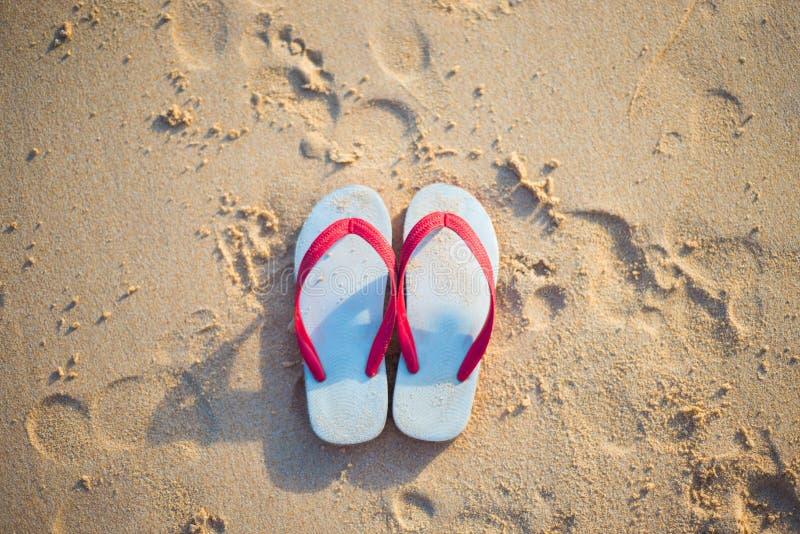 Röd och vit sandal på stranden fotografering för bildbyråer