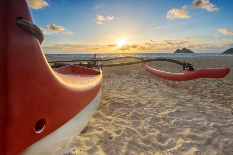 Röd och vit utriggarekanot på stranden royaltyfri fotografi