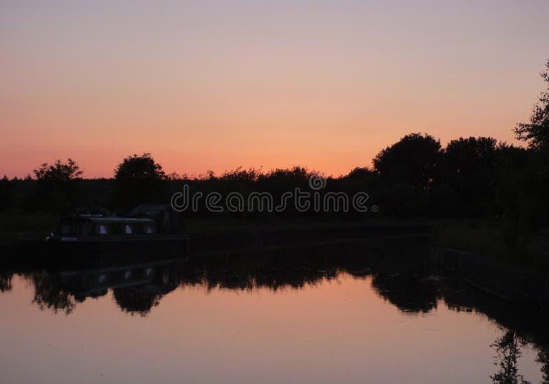 Röd/orange solnedgång, aftonlandskap som ser över en sjö, foto som tas i UK arkivfoto