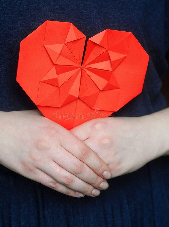 Röd origamihjärta i händer för flicka` s royaltyfria bilder