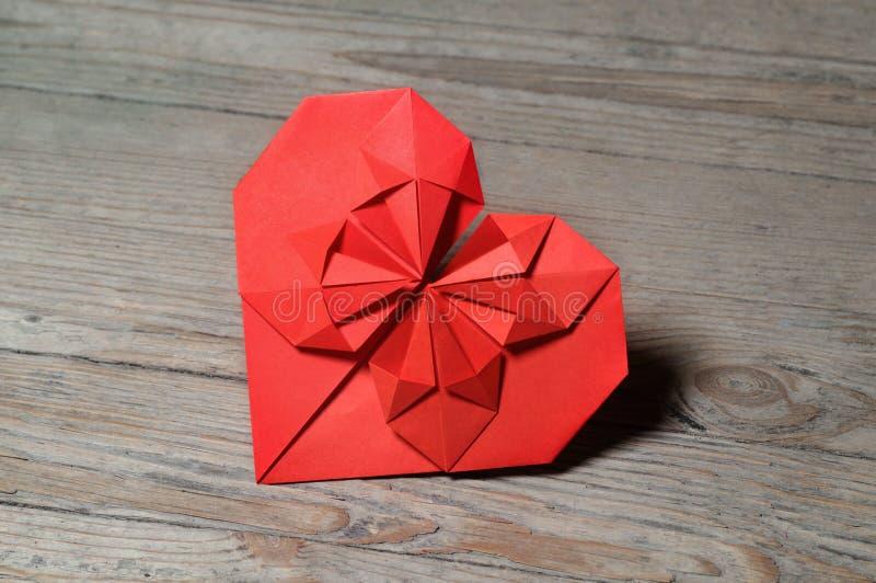 Röd origamihjärta på träbakgrund fotografering för bildbyråer