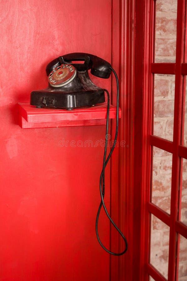 Röd på engelska stil för telefonbås Brittisk telefonask med den svarta retro telefonen som står i den arkivfoto