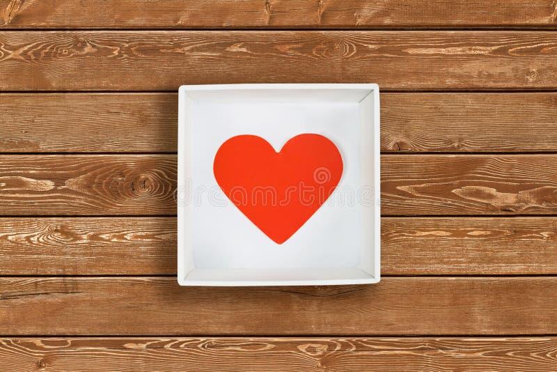Röd pappers- hjärta i den vita kartongen på träväggbakgrund Lekmanna- lägenhet arkivfoton