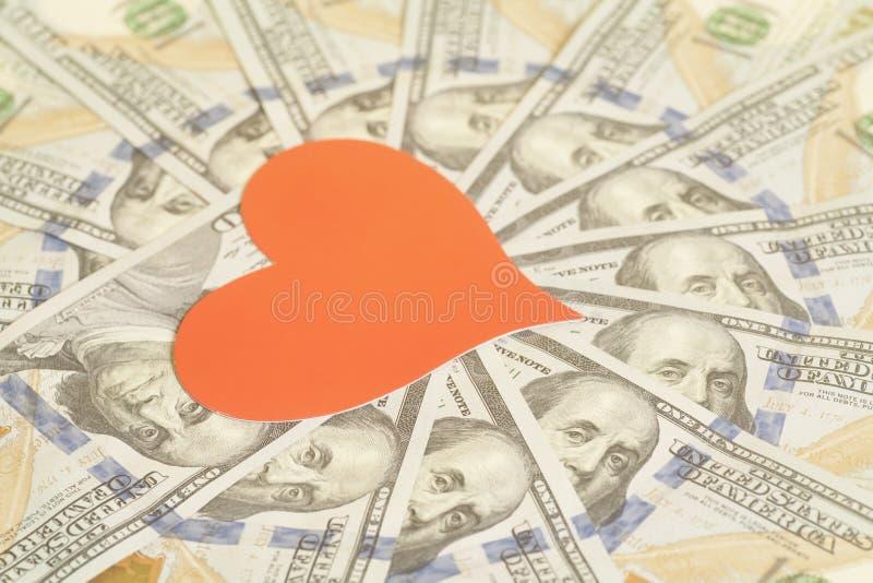 Röd pappers- hjärta och hundra bakgrund för dollarräkningar arkivfoto