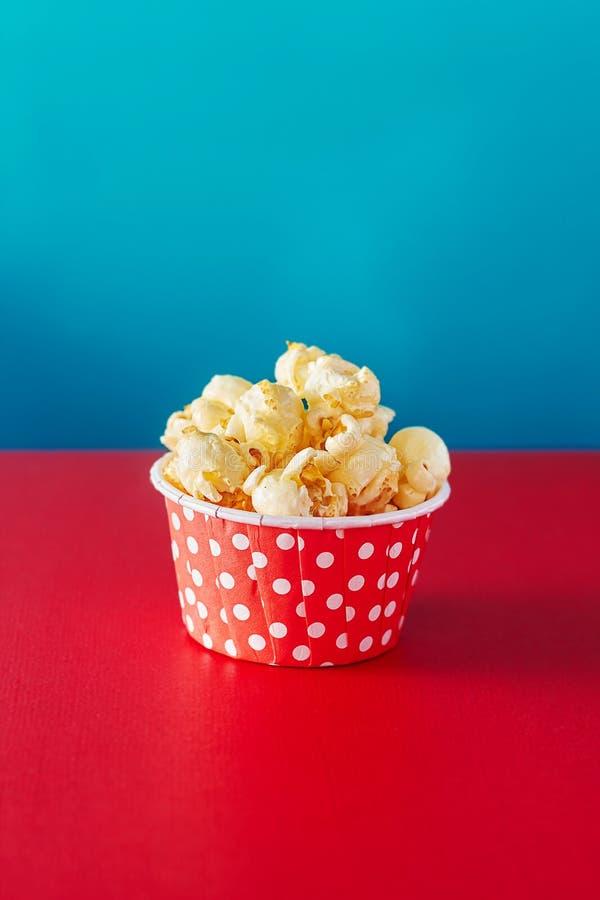 Röd pappers- kopp med popcorn mot vibrerande bakgrund royaltyfri foto
