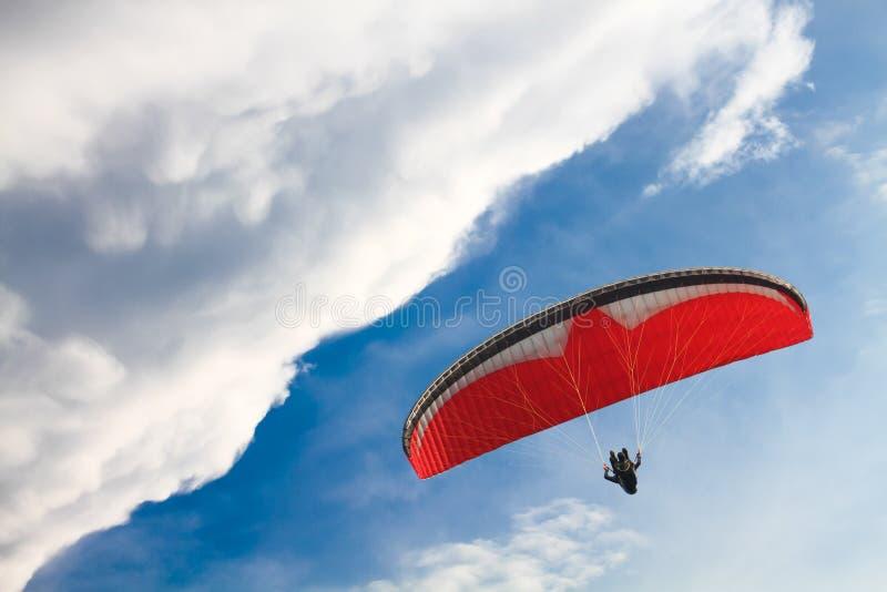 Röd Paragliding mot blå himmel med vita moln arkivbild