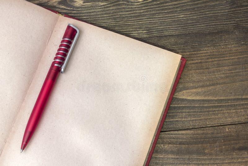 Röd penna med boken arkivfoto