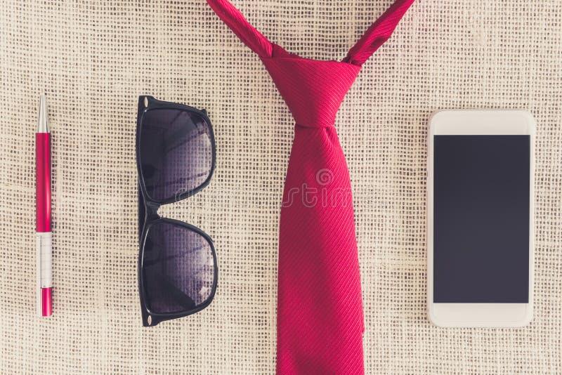 Röd penna, smartphone, solglasögon på ren säckväv med den röda halsen royaltyfri bild